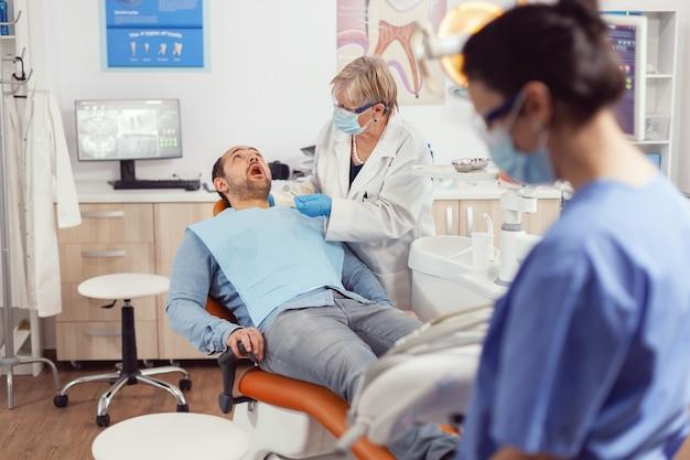 口を開けて歯科用椅子に座っている病気の患者