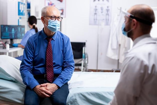 病院の診察室でcovidに対する保護マスクを着用して診察中に医師と話している病気の患者