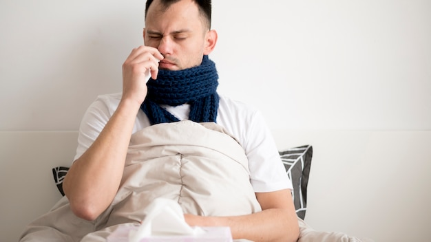 Sick person staying in bed wrapped in a blanket