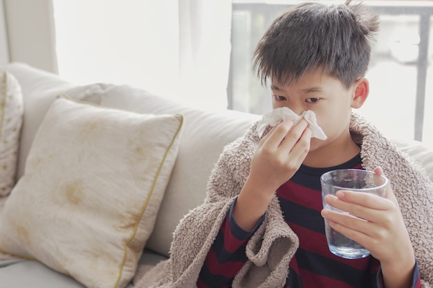Sick preteen boy blowing nose and holding glass of water at home