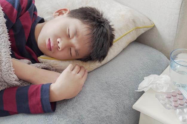 Больной малолетний мальчик отдыхает на диване с лекарствами дома, концепция здравоохранения