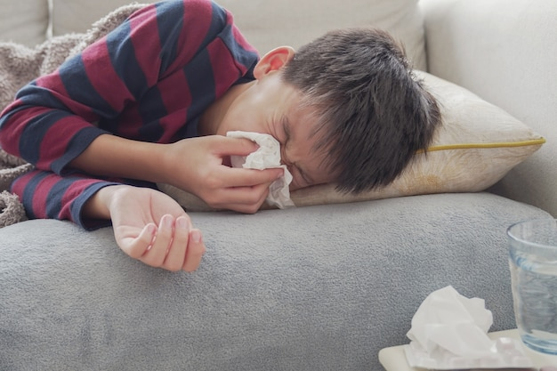 Sick preteen boy sneezing lying on sofa at home