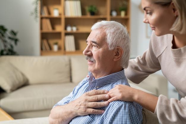 Больной пенсионер с седыми волосами, держащий руку своей молодой осторожной дочери, склонившейся к нему, стоя рядом