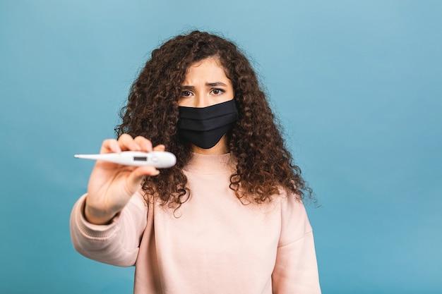 病気の悲しい若い女性、パンデミック検疫中にコロナウイルスウイルスcovid-19から安全な滅菌顔医療マスク、温度計を保持