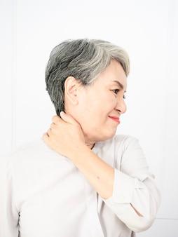 首に触れる病気の高齢者の高齢女性は、肩と首の痛みがあります。医療と医学の概念