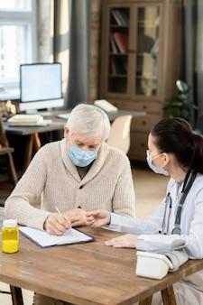 Больной пожилой мужчина в маске и повседневной одежде подписывает медицинский документ, сидя за столом перед молодой женщиной-врачом в гостиной