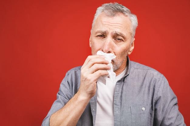 Больной старший человек, сморкающийся с тканью. грипп, аллергия