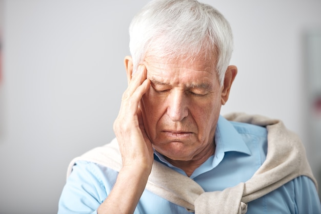 Sick senior man with whte hair and closed eyes touching head while having headache or expressing tiredness