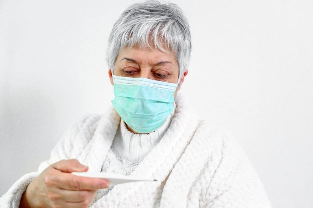 Sick senior woman holding thermometer sit on bed.