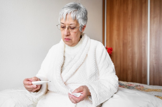 Sick senior woman holding tissue and thermometer sit on bed.