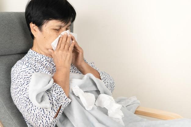 더러운 조직으로 아픈 고위 여자. 담요 모직을 입고 아픈 사람이 소파에 누워