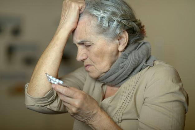 두통이 있는 약을 든 아픈 노인 여성