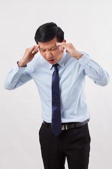 Больной, напряженный, перегруженный работой мужчина с головной болью, мигренью, головокружением, похмельем