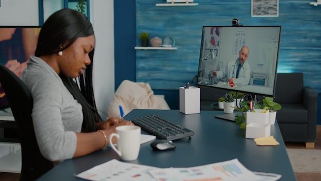 Больной студент-пациент обсуждает симптомы болезни с врачом во время онлайн-консультации по телемедицине с видеозвонком, сидя за столом в гостиной
