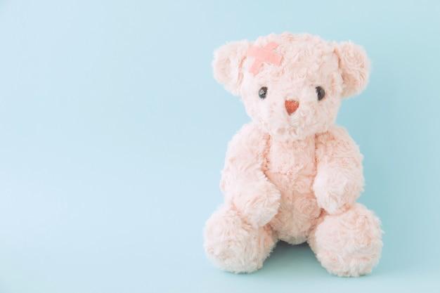 Sick teddy bear with bandage on blue background