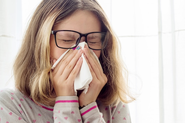 Sick teen girl with handkerchief at home