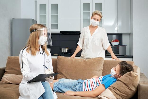 Sick teenager boy lying on sofa while doctor doing checkup