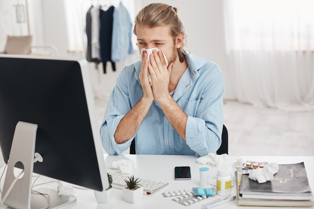 Sick and tired bearded office worker has suffering expression, has running nose, sneezing, coughing, because of flu, surrounded by pills and drugs, tries to concentrate and finish work quicker
