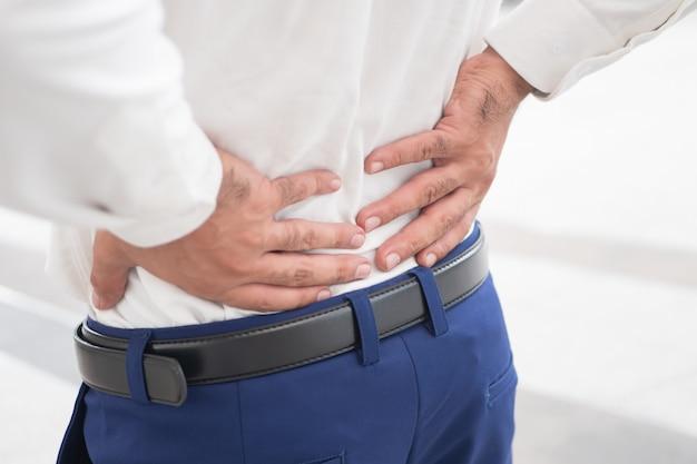 Больной нездоровый азиатский мужчина, страдающий от боли в спине, проблемы с позвоночником, грыжи межпозвоночного диска, вывиха или смещения позвоночного диска, офисного синдрома