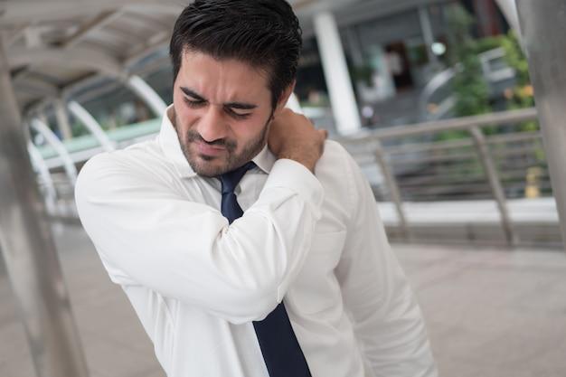 Больной нездоровый азиатский мужчина страдает от боли в плече, ригидности плеча, артрита, подагры, офисного синдрома