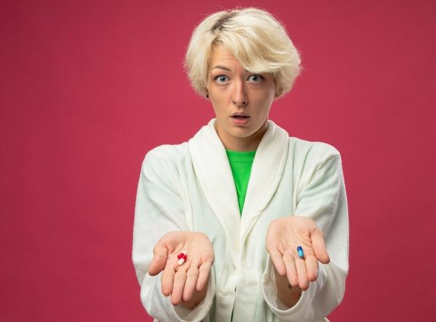 Malata malsana donna con i capelli corti sensazione di malessere che mostra le pillole tra le braccia con espressione confusa avendo dubbi in piedi su sfondo rosa