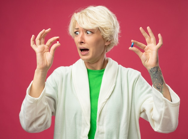Sick unhealthy woman with short hair feeling unwell showing pillswith confused expression having doubts stressed and worried standing over pink background