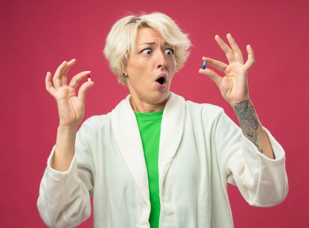 Donna malsana malata con capelli corti sensazione di malessere mostrando pillole con espressione confusa avendo dubbi stressati e preoccupati cercando di fare una scelta in piedi su sfondo rosa