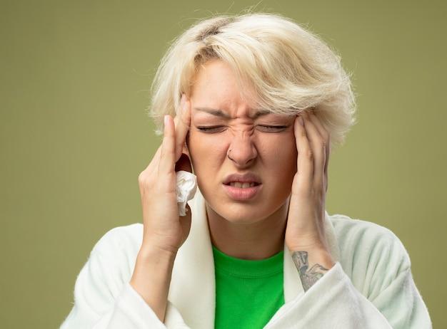 明るい背景の上に立っている強い頭痛に苦しんでいる彼女の寺院を苦しめている短い髪の病気の不健康な女性
