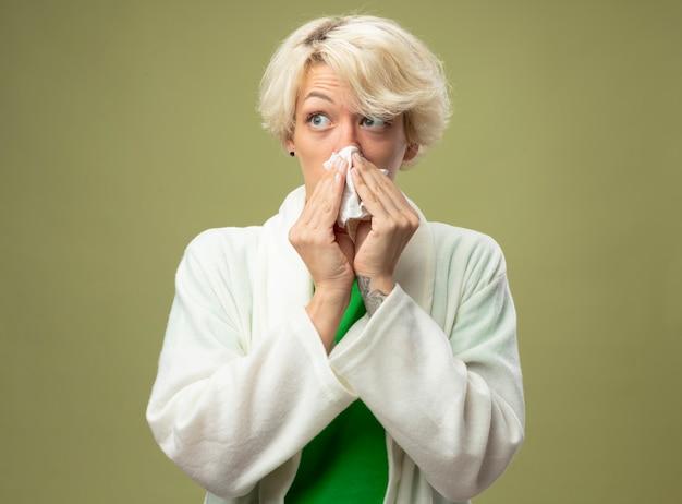 Malata malsana donna con i capelli corti sensazione di malessere pulendosi il naso con un fazzoletto in piedi sopra la parete chiara
