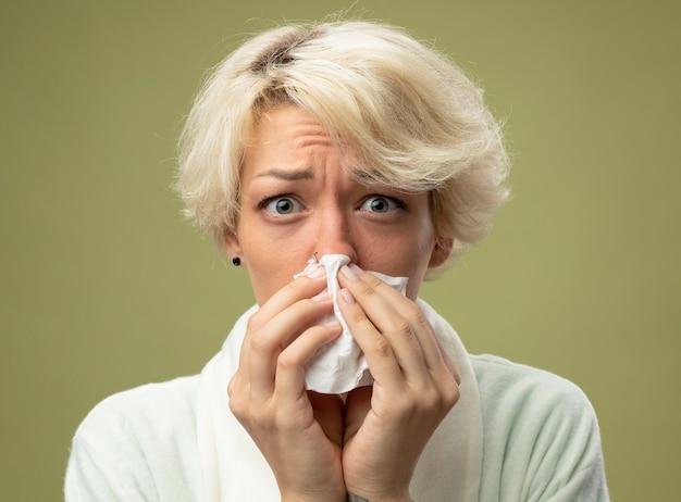 Donna malsana malata con capelli corti sensazione di malessere asciugandosi il naso con un fazzoletto in piedi sopra la parete chiara
