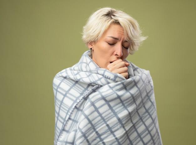 Больная нездоровая женщина с короткими волосами чувствует себя плохо, завернувшись в одеяло, кашляет, стоя над светлой стеной