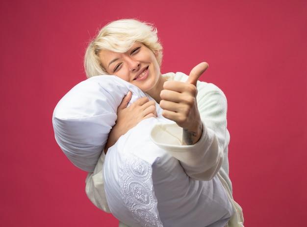 Больная нездоровая женщина с короткими волосами, обнимающая подушку, чувствует себя лучше, улыбается, показывает палец вверх, стоя над розовой стеной