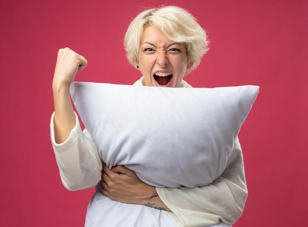 枕を抱き締める短い髪の病気の不健康な女性は、ピンクの背景の上に立って、握りこぶしを握り締めて狂った幸せを叫んで気分が良くなります