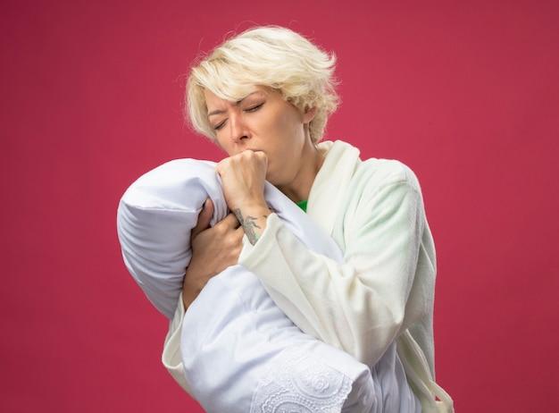 Больная нездоровая женщина с короткими волосами обнимает подушку, чувствуя недомогание и кашляет, стоя над розовой стеной