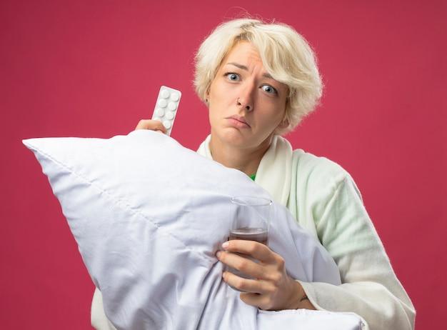 짧은 머리 포옹 베개와 아픈 건강에 해로운 여자는 물과 약의 유리를 들고 불쾌한 느낌이 분홍색 벽 위에 서서 화가 난다.