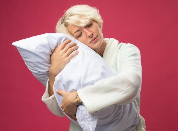 Больная нездоровая женщина с короткими волосами обнимает подушку с закрытыми глазами и мечтает стоять над розовой стеной