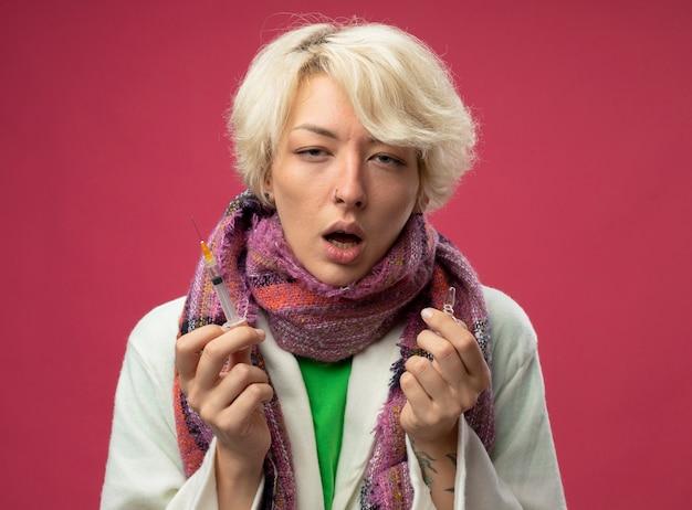 Больная нездоровая женщина с короткими волосами в шарфе плохо себя чувствует, держа ампулу и шприц на розовом фоне
