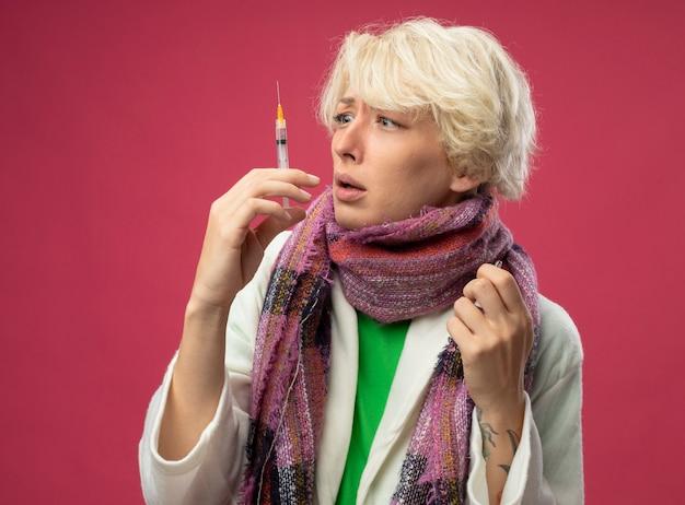 Больная нездоровая женщина с короткими волосами в шарфе чувствует себя нездоровой, держа ампулу, глядя на шприц, смущенная и испуганная, стоя над розовой стеной