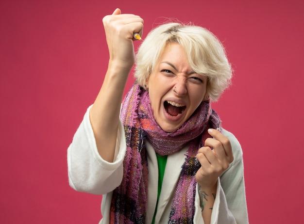 Больная нездоровая женщина с короткими волосами в шарфе чувствует себя нездоровой, держа ампулу, показывая шприц, кричащий с агрессивным выражением лица, сумасшедший, сумасшедший, стоя на розовом фоне