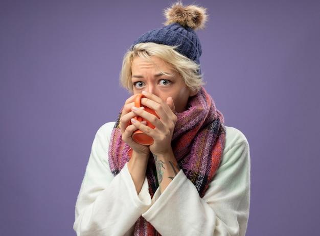 Больная нездоровая женщина с короткими волосами в теплом шарфе и шляпе чувствует себя плохо, пьет горячий чай, стоя над фиолетовой стеной