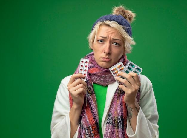 따뜻한 스카프와 모자에 짧은 머리를 가진 아픈 건강에 해로운 여자는 약이 녹색 벽 위에 서서 화가 나고 불행한 상태로 물집을 들고 몸이 좋지 않습니다.