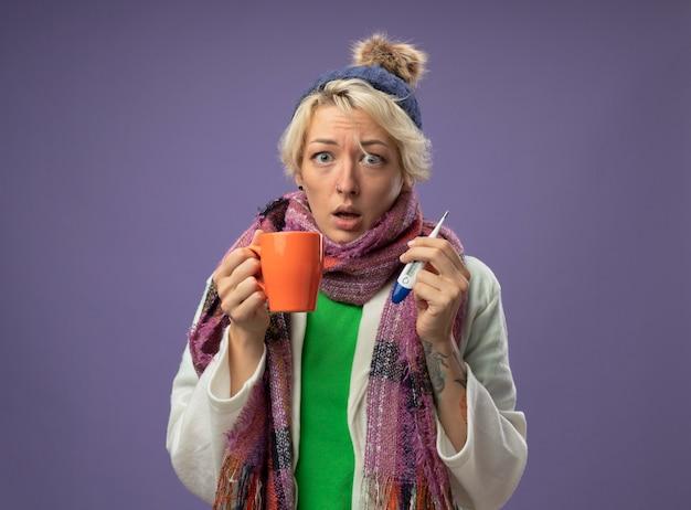 Больная нездоровая женщина с короткими волосами в теплом шарфе и шляпе чувствует себя плохо, держа чашку горячего чая и термометр, глядя в камеру, глядя в камеру, обеспокоенная стоя на фиолетовом фоне