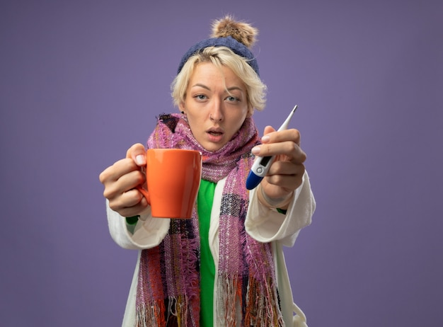 따뜻한 스카프와 모자에 짧은 머리를 가진 아픈 건강에 해로운 여자는 보라색 배경 위에 서있는 카메라를보고 뜨거운 차와 온도계의 컵을 들고 기분이 좋지 않습니다.