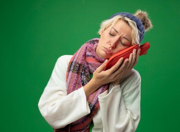 暖かいスカーフと帽子の短い髪の病気の不健康な女性は、緑の背景の上に暖かい立っていることを維持するために顔の近くに水筒を持って気分が悪い