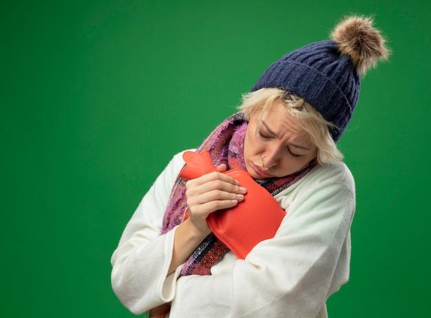 따뜻한 스카프와 모자에 짧은 머리를 가진 아픈 건강에 해로운 여자가 녹색 배경 위에 따뜻한 서를 유지하기 위해 물병을 들고 몸이 좋지 않은 느낌