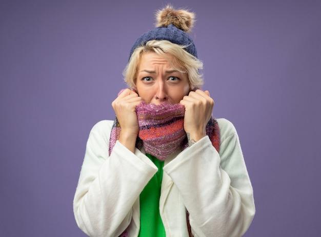 따뜻한 스카프와 모자에 짧은 머리를 가진 아픈 건강에 해로운 여자는 보라색 배경 걱정