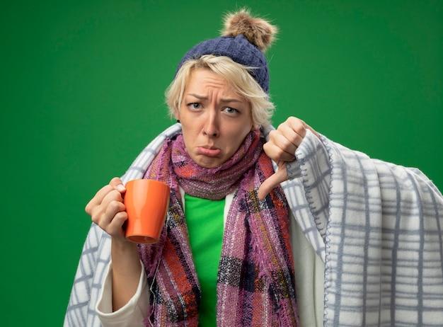 Больная нездоровая женщина с короткими волосами в теплом шарфе и шляпе чувствует себя нездоровой, завернувшись в одеяло, держит чашку чая с несчастным лицом, показывая пальцы вниз, стоя у зеленой стены