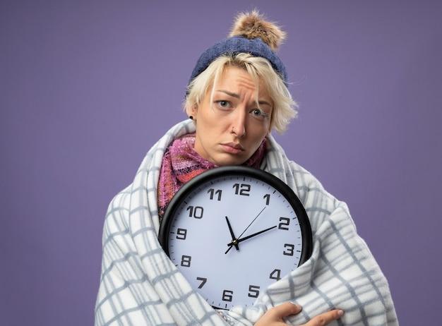Больная нездоровая женщина с короткими волосами в теплом шарфе и шляпе чувствует себя нездоровой, завернувшись в одеяло, держит настенные часы и смотрит в камеру с грустным выражением лица на фиолетовом фоне