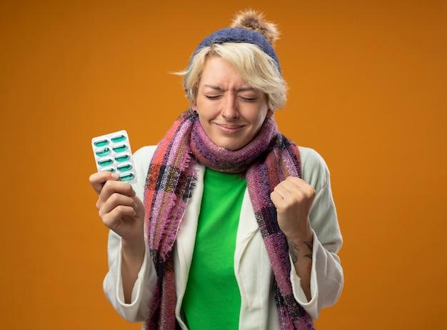 Больная нездоровая женщина с короткими волосами в теплом шарфе и шляпе, держащая блистер с таблетками, счастливая и взволнованная, с закрытыми глазами, сжимая кулак, стоя на оранжевом фоне