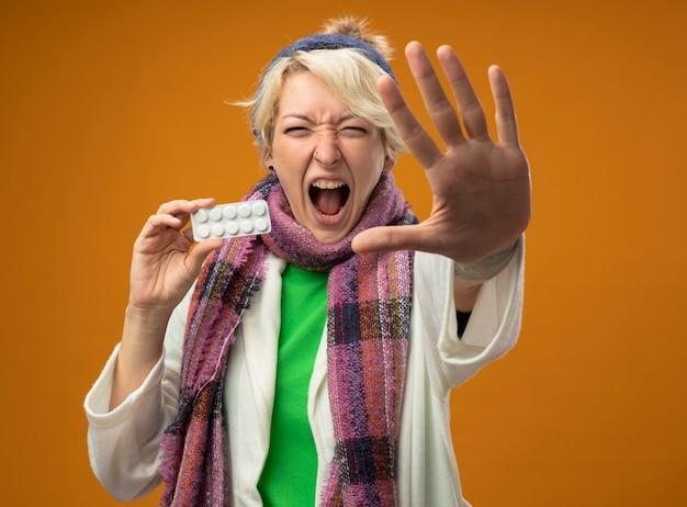 Больная нездоровая женщина с короткими волосами в теплом шарфе и шляпе, держащая блистер с таблетками, делает стоп-жест рукой, кричит, стоя на оранжевом фоне